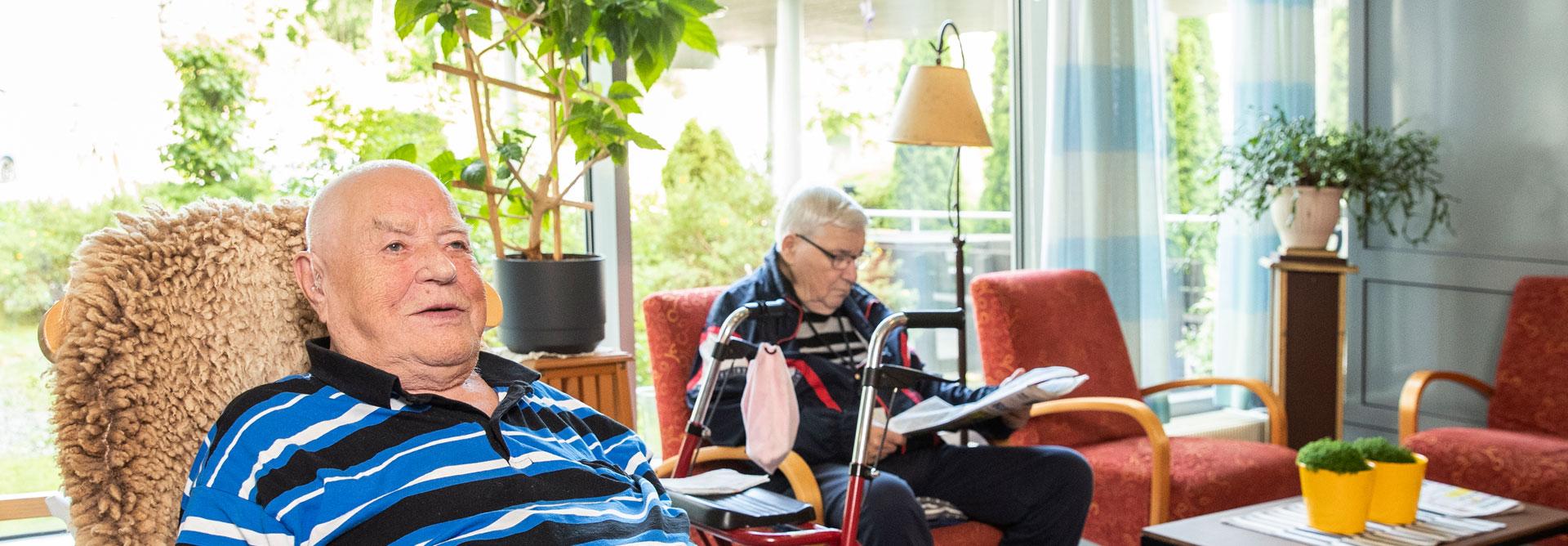 Naantalin palvelutalon kaksi asukasta istuvat aulassa